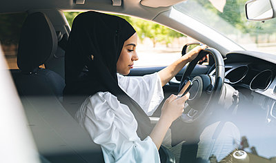 Woman text messaging through mobile phone while driving car - p300m2293559 by Jose Carlos Ichiro