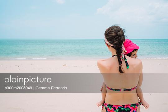 Thailand, Koh Lanta, back view of woman and little daughter on the beach - p300m2003949 von Gemma Ferrando