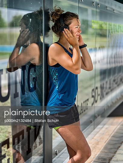 Young sportive woman wearing headphones - p300m2132484 by Stefan Schurr