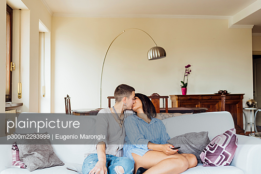 Affectionate girlfriends kissing while sitting on sofa in living room - p300m2293999 by Eugenio Marongiu