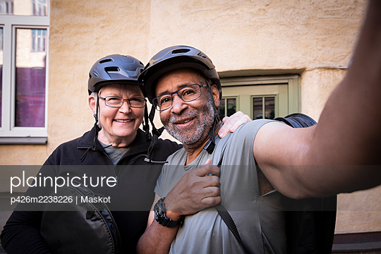 Active senior couple taking selfie while wearing cycling helmet in balcony - p426m2238226 by Maskot