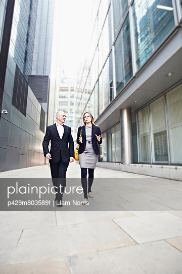 Businessman and businesswoman walking past office buildings - p429m803589f by Liam Norris