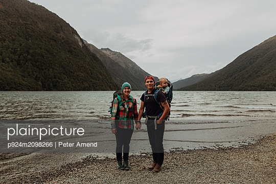 Parents with baby on beach, Queenstown, Canterbury, New Zealand - p924m2098266 by Peter Amend