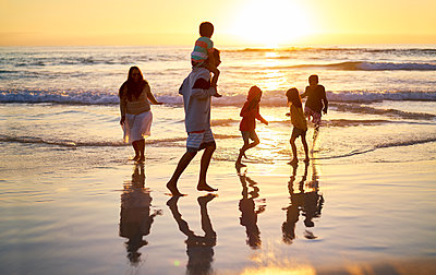 Family wading in surf on idyllic ocean beach at sunset - p1023m2200816 by Trevor Adeline