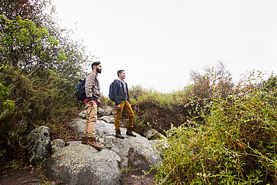Two young men carrying backpacks hiking. - p1100m1038888 by Mint Images