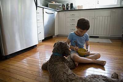Dog watching boy eat cereal on kitchen floor - p1192m1078226f by Hero Images