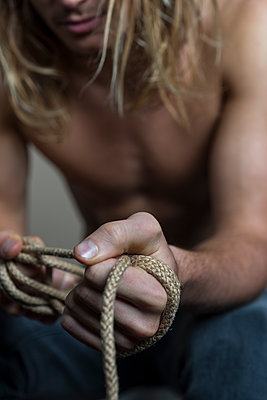 Young topless man with messy hair pulling a length of rope. - p1433m1586829 by Wolf Kettler