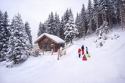 Austria, Altenmarkt-Zauchensee, family with sledges at wooden house at Christmas time - p300m2042020 by Hans Huber