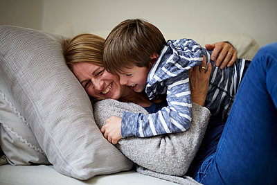 Mother and son cuddling on the couch - p300m2103575 von Rainer Berg