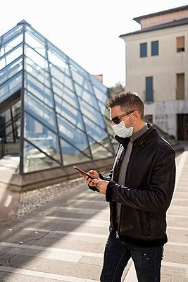 Man wearing face mask using mobile phone on footpath during pandemic - p300m2282318 by Mauro Grigollo