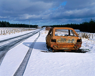 Abandoned car in snow by road - p92410549f by Image Source
