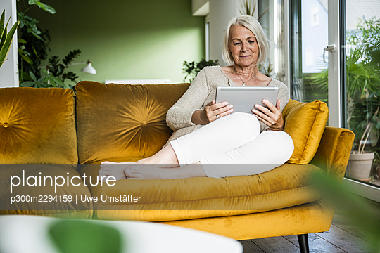 Woman using digital tablet while sitting in living room - p300m2294159 by Uwe Umstätter