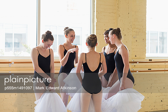Girls standing and talking in ballet studio - p555m1491097 by Mark Edward Atkinson
