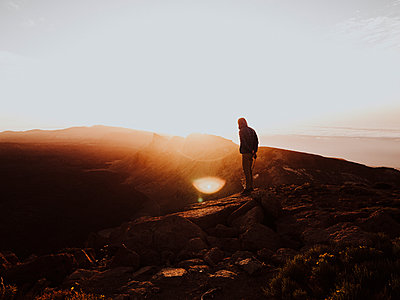 A man stands on mountain top watching sunrise - p1166m2129905 by Cavan Images