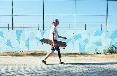 Young man with leg prosthesis walking and holding skateboard - p300m2140525 by Jose Luis CARRASCOSA