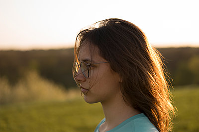 Young woman with eyeglasses outdoors - p552m1564909 by Leander Hopf