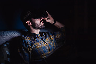 Bearded mid adult man sitting on sofa in darkness looking up through virtual reality headset - p924m2097480 by Eugenio Marongiu