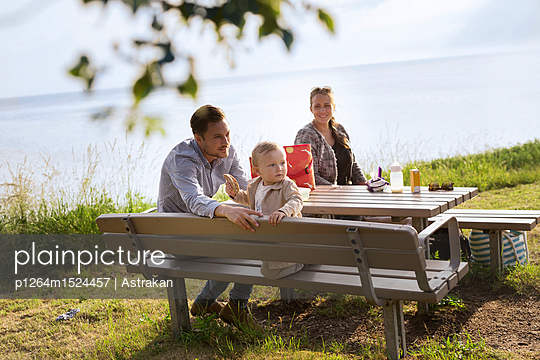 Parents with son (18-23 months) sitting by picnic table - p1264m1524457 by Astrakan