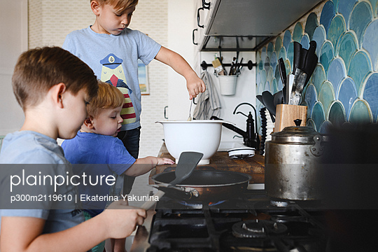 Three brothers cooking pancakes in the kitchen - p300m2119610 by Ekaterina Yakunina