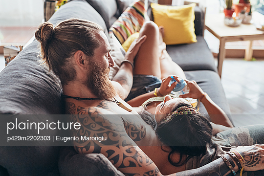 Bearded tattooed man with long brunette hair and woman with long brown hair cuddling on a sofa. - p429m2202303 by Eugenio Marongiu