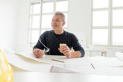Architekt schaut hoch und trinkt einen Kaffee am Zeichentisch - p1212m1538883 von harry + lidy