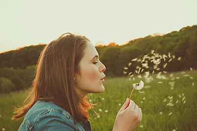 Profile of teenage girl blowing blowball - p300m2113886 von Annie Hall
