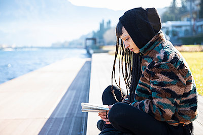 Young woman sitting on bench reading a book at Lake Como, Como, Italy - p300m2167422 by 27exp