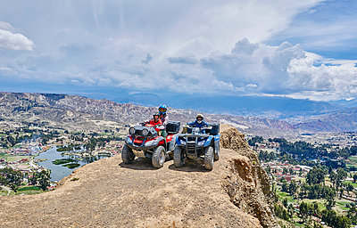 Mother and sons on top of mountain, using quad bikes, La Paz, Bolivia, South America - p429m1557395 by Stephen Lux