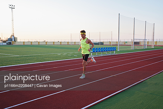young man trains running on new and red tracks - p1166m2208447 by Cavan Images