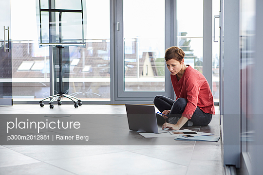 Businesswoman sitting on the floor in office using laptop - p300m2012981 von Rainer Berg