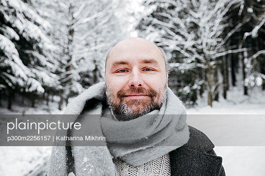 Smiling mature man wearing scarf against bare trees in sow - p300m2256157 by Katharina Mikhrin