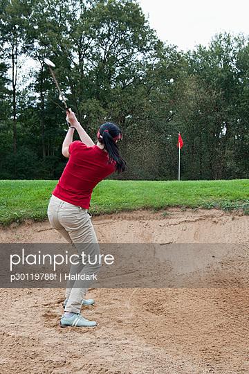 A female golfer hitting a ball out of a sand trap - p30119788f by Halfdark