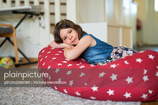 Girl lying on bean bag - p312m2086380 by Victoria Henriksson