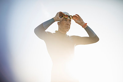 A swimmer in a wetsuit and swimming hat, adjusting his swimming goggles.  - p1100m1112329f by Mint Images