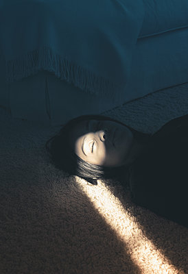Woman Lying on Floor in a Beam of Sunlight - p1617m2200371 by Barb McKinney
