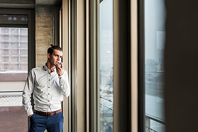Young businessman using cell phone at the window - p300m1356463 by Uwe Umstätter