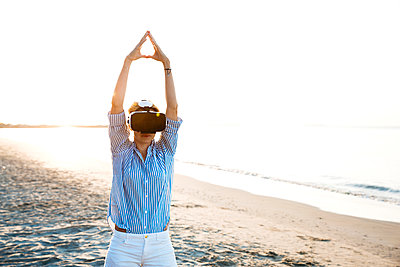Blonde woman doing kind of yoga exercises on a beach in thailand with 3D virtual reality goggles - p300m2080376 by Epiximages