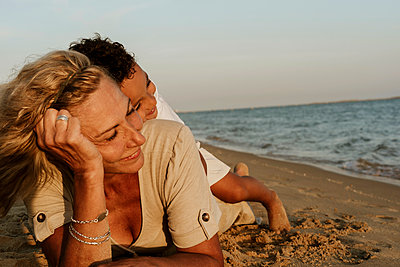 Grandmother lying on sand while grandson sleeping on her back at beach during sunset - p300m2221151 by Eloisa Ramos