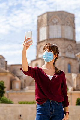 Woman taking selfie through mobile phone against structure during pandemic - p300m2264690 by Albert Martínez