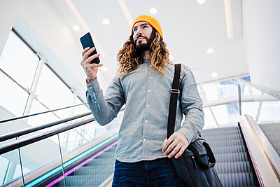 Man with long hair holding mobile phone while moving on escalator - p300m2274059 by Eva Blanco