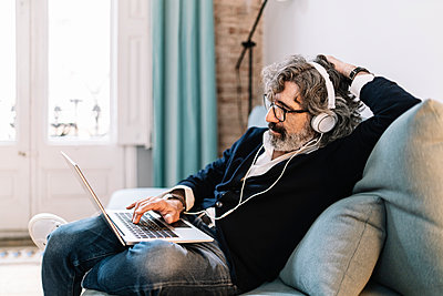 Relaxed senior man with headphones using laptop while sitting on sofa at home - p300m2277123 by COROIMAGE