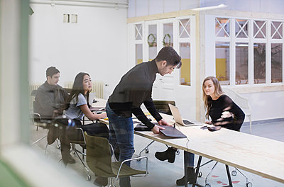 Four people discussing in creative office seen through glass wall - p426m1407190 by Maskot