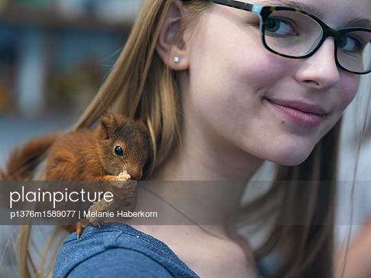 Knabberndes Eichhörnchen auf Schulter - p1376m1589077 von Melanie Haberkorn