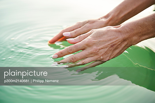 Close-up of woman's hands touching water of a lake - p300m2140681 by Philipp Nemenz