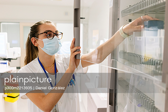 Female doctor taking medicines from cabinet in pharmacy at hospital - p300m2213935 by Daniel González