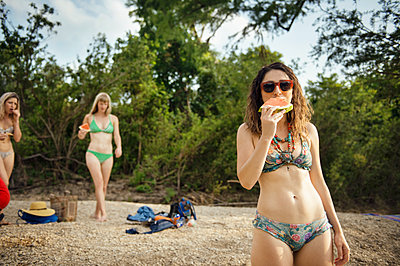 Portrait of woman eating watermelon slice with friends at beach - p1166m1174262 by Cavan Images