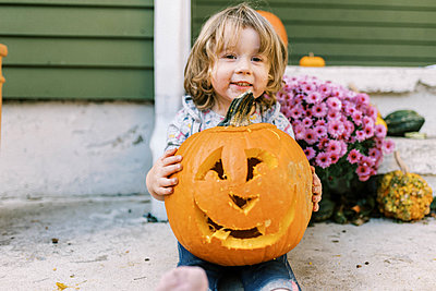 Little toddler girl holding her carved pumpkin lantern proudly - p1166m2218611 by Cavan Images