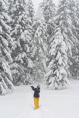 Finland, Kuopio, woman catching snowflakes in winter forest - p300m2103700 by Petra Silie