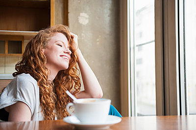 Portrait of happy young woman in cafe - p429m896532f by Daniel Ingold