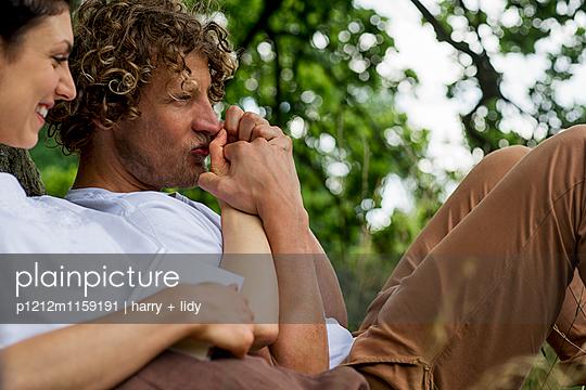 Junger Mann küsst die Hand einer jungen Frau - p1212m1159191 von harry + lidy